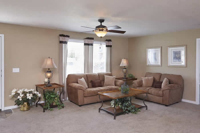 living room of Brookwood model with beige carpet, ceiling fans, and large windows