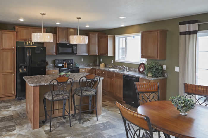 kitchen and dining room of Brookwood model with dining room table, island bar, wood cabinets, fridge, oven, and sink.