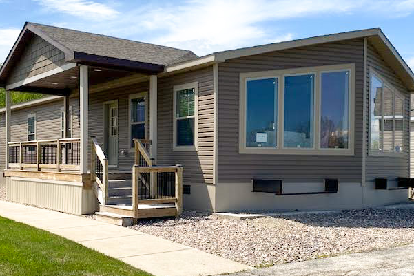 Outside, front view of Hickory Ridge model. Brown siding, large picture windows, rock landscaping, and covered front porch