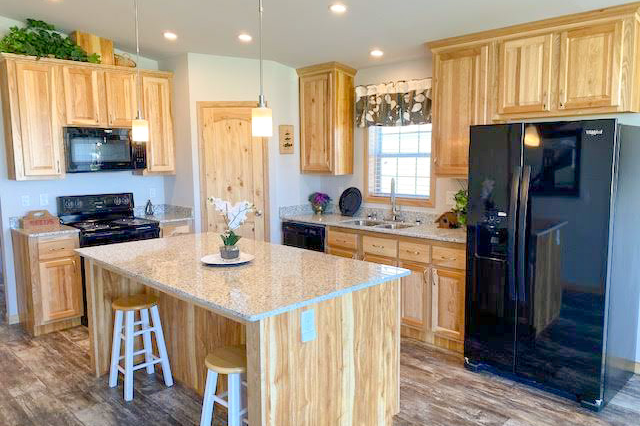 kitchen with island bar, oak cabinets, fridge, oven, and sink in Hickory Ridge model