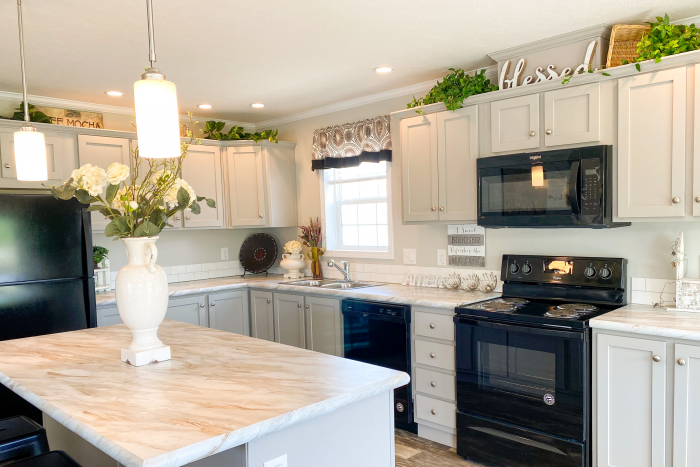 Kitchen with white cabinets, marble countertops, island bar, fridge, oven, dishwasher, and sink in Pineview model