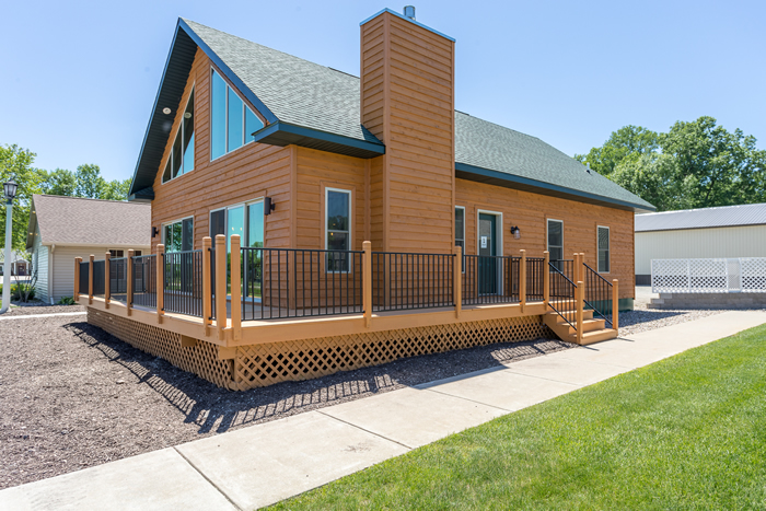 Side outdoor view of Aspen model. Natural wood siding, chimney, and uncovered porch.