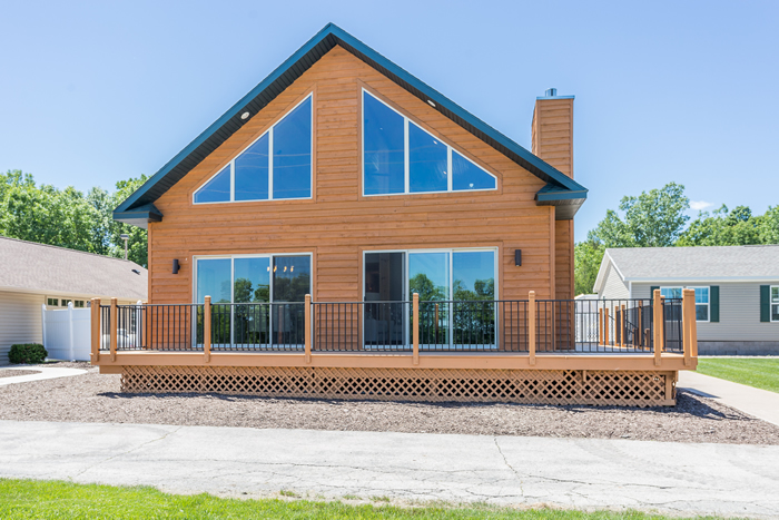 outdoor view of front of Aspen model. Large, floor to ceiling windows, natural wood siding, chimney, and uncovered porch.
