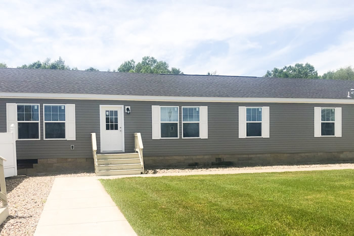 Outside of modular home model Hampton. With gray siding and white trim on windows and front door.
