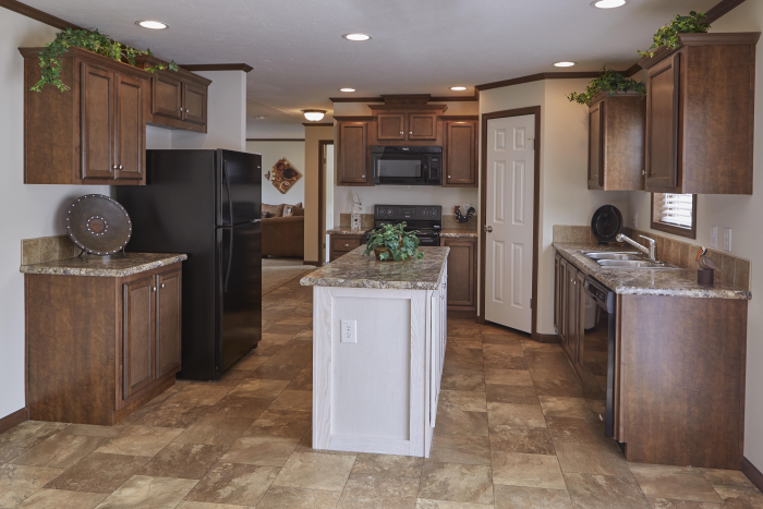 Kitchen in Montclair model. Tile floors, dark wood cabinets, and island