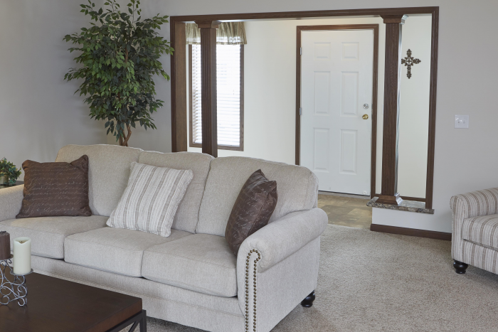 Front entrance with a white couch and a white door in Montclair model